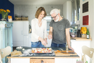 Mature couple preparing a pizza in kitchen at home - MOEF00987