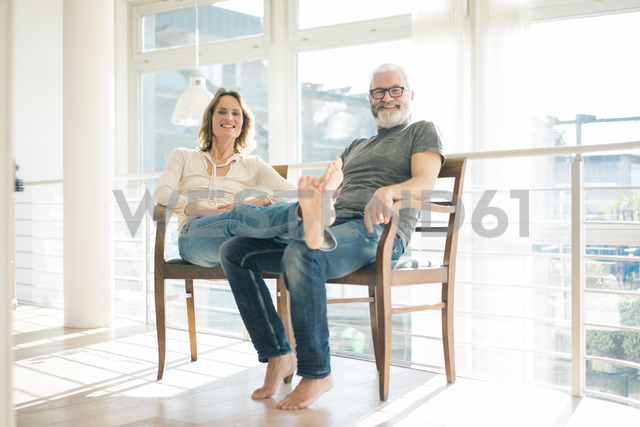 Portrait of relaxed mature couple sitting on chairs at home - MOEF00990