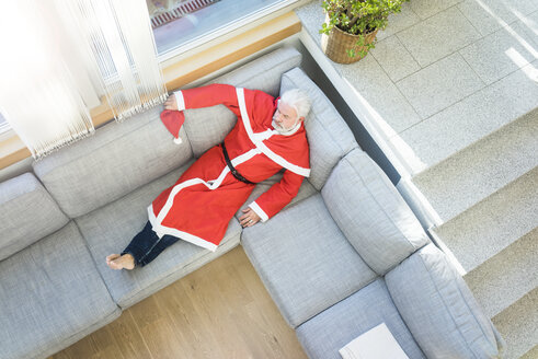 Bearded mature man wearing Santa costume lying on couch in living room - MOEF00999