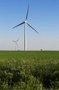Windmills on grassy field against clear blue sky - CAVF24935