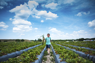Boy holding root vegetables while running at organic farm against cloudy sky - CAVF25061