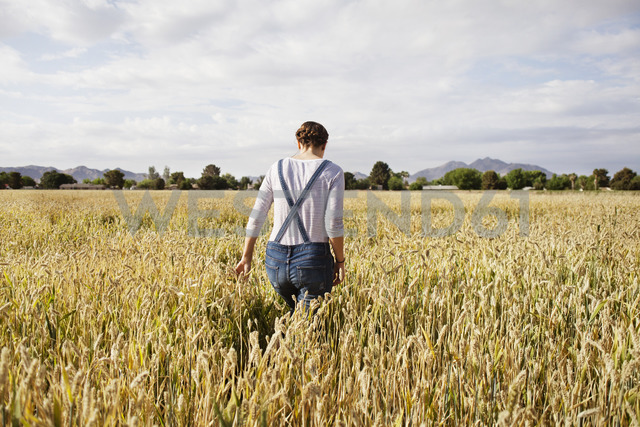 Rear view of female farmer walking on cultivated field - CAVF25112