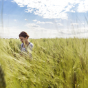 Woman in cultivated wheat field against clear sky - CAVF25115