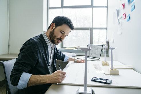 Businessman working on wind turbine models in office - CAVF25202