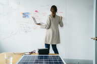 Rear view of businesswoman writing on whiteboard while working over solar panels in office - CAVF25214