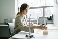 Side view of businesswoman arranging wind turbine models on desk - CAVF25217