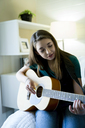 Teenage girl playing guitar in bedroom - CAVF25319
