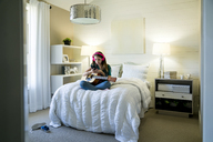Teenage girl using smart phone while sitting with guitar on bed in bedroom# - CAVF25325