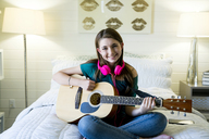 Portrait of happy teenage girl playing guitar in bedroom - CAVF25328