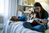 Girl using smart phone while sister playing guitar on bed - CAVF25331