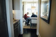 Senior couple sitting at financial advisor's office seen through doorway - CAVF25352