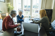 Financial advisor explaining plan to senior couple on tablet computer while sitting in office - CAVF25355