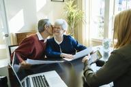 Senior man kissing senior woman while sitting in financial advisor's office - CAVF25367