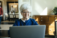 Senior woman using laptop computer at home with senior man in background - CAVF25373