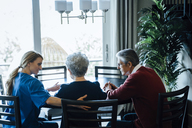 Home caregiver discussing with senior couple while sitting at dining table - CAVF25388