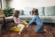Boy wearing virtual reality simulator playing with sister sitting on rocking horse at home - CAVF25454