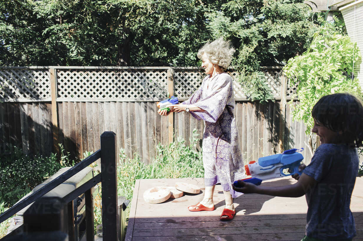 Grandmother and grandson playing with squirt guns while standing in yard - CAVF25478 - Cavan Images/Westend61