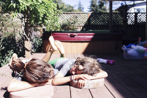 Brothers resting while lying on floorboard in yard during sunny day - CAVF25481