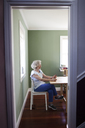 Senior woman using smart phone while sitting on chair at home seen through doorway - CAVF25484