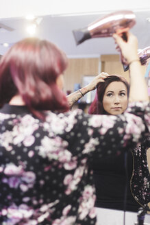 Reflection of woman using hair dryer at salon seen in mirror - CAVF25538