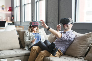 Colleagues wearing virtual reality simulator while sitting on sofa in office - CAVF25598