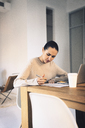 Businesswoman writing while sitting at desk in office - CAVF25613
