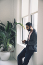 Businessman using smart phone while leaning on window sill in office - CAVF25631