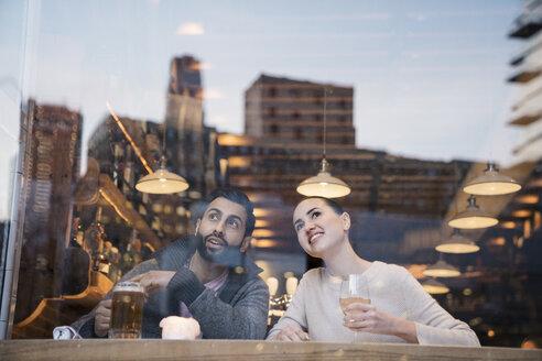 Couple enjoying drinks while looking away seen through restaurant window - CAVF25643