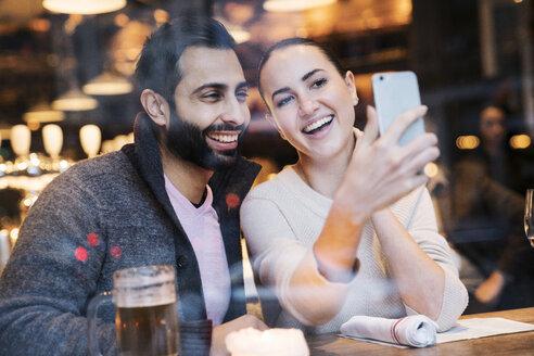 Happy woman with boyfriend using mobile phone seen through restaurant window - CAVF25646