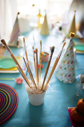 Various paint brushes in container on decorated table at home - CAVF25673