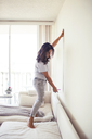 Side view of woman measuring wall while standing on sofa at home - CAVF25715