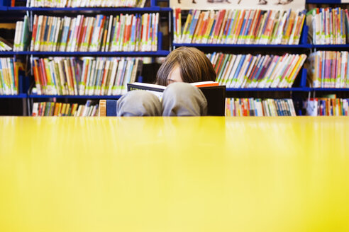 Boy reading book in library - CAVF25742