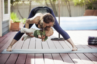 Mother holding baby and doing yoga at backyard - CAVF25796