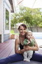 Portrait of mother holding baby boy while sitting with legs apart at backyard - CAVF25799