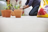 Low section of man gardening in balcony - CAVF25859