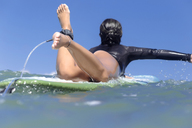 Indonesia, Bali, female surfer lying on surfboard - KNTF01101