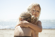 Sisters embracing at beach on sunny day - CAVF25931