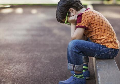 Side view of sad boy wearing eyeglasses sitting on curb by footpath - CAVF25976