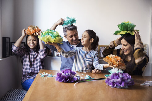 Happy family playing with homemade paper flowers while sitting at table - CAVF26048