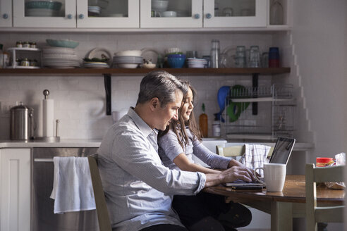Daughter sitting with father using laptop computer in kitchen at home - CAVF26075