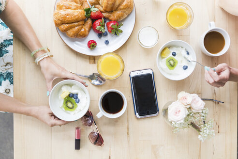 Overhead view of friends having breakfast at table in cafe - CAVF26147