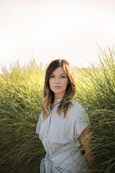 Portrait of confident woman standing by grass against clear sky - CAVF26309
