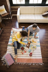 High angle view of couple eating food while sitting on carpet at home - CAVF26315