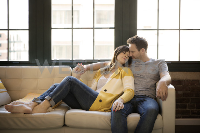 Couple relaxing on sofa at home - CAVF26318 - Cavan Images/Westend61