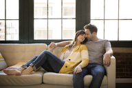 Couple relaxing on sofa at home - CAVF26318