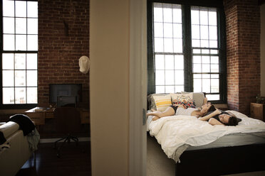 Couple relaxing on bed at home - CAVF26324