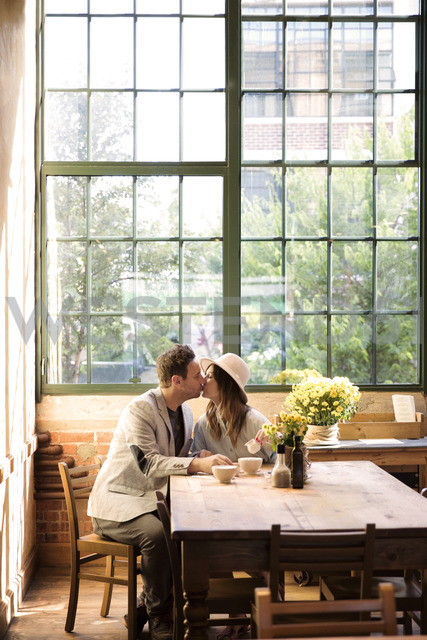 Couple kissing while sitting by table in restaurant - CAVF26330 - Cavan Images/Westend61
