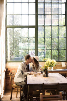 Couple kissing while sitting by table in restaurant - CAVF26330