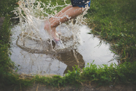 Low section of carefree boy jumping in puddle on grassy field - CAVF26393