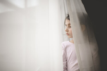 Girl with eyes closed standing by window curtain at home - CAVF26411